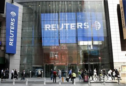 Pedestrians walk past the Reuters building in Times Square in New York, May 15, 2007. REUTERS/Gary Hershorn
