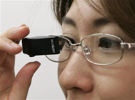 A Scalar employee demonstrates the company's new T3-F wearable video display in Tokyo May 21, 2007. Scalar says it will begin selling the T3-F, which attaches to eyeglasses and gives the wearer a view equivalent to watching a 28-inch screen from two meters away, from May 22 for 98,000 yen (US$810). REUTERS/Michael Caronna