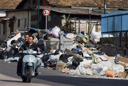 Youths ride a scooter beside mounds of garbage during a refuse collection crisis in the southern Italian city of Naples May 19, 2007. Hundreds of rubbish bags bake in the sun, a putrid stench hangs over streets of pastel-colored houses and apartment blocks in the small Italian town of Cupua. REUTERS/Dario Pignatelli