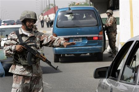 An Iraqi soldier directs traffic while a fellow soldiers checks a vehicle at a checkpoint in Baghdad, June 3, 2007. REUTERS/Ali Jasim