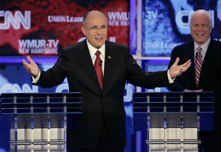 Republican presidential candidate and former New York City Mayor Rudolph Giuliani (L) jokes about being the last one left onstage after lightning loudly struck the debate hall and scattered the candidates as U.S. Sen. John McCain (R-AZ), watches during a debate at Saint Anselm College in Manchester, New Hampshire June 5, 2007. REUTERS/Brian Snyder