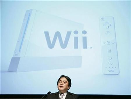 Nintendo President Satoru Iwata speaks at an earnings news conference in front of a screen showing the company's Wii game console in Tokyo in this April 27, 2007 file photo. Nintendo Co.'s Wii game console outsold Sony Corp.'s PlayStation 3 by more than five to one in Japan last month, Japanese game magazine publisher Enterbrain said, casting a shadow over a turnaround in Sony's game business. REUTERS/Michael Caronna
