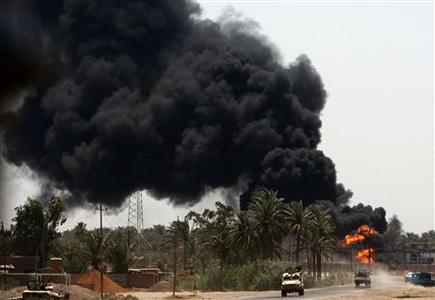 Smoke rises from an Iraqi police and U.S. army base after Iraqi insurgents hit a fuel tank with mortar shell near the town of Al-Meshahda, some 50 km (31 miles) north of Baghdad, June 10, 2007. REUTERS/Goran Tomasevic