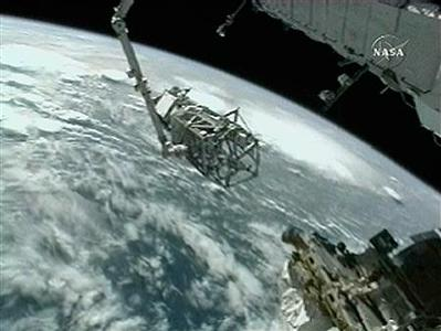 The starboard S3/S4 truss segment is attached to the International Space Stations' arm over the Earth in this NASA TV June 11, 2007 video grab. A team of spacewalkers will install the (S3/S4) truss segments during todays planned six-hour spacewalk. REUTERS/NASA TV