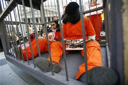 A demonstrator holds a sign during the International Day to Shut Down Guantanamo protest, in New York January 11, 2007. The U.S. war crimes tribunals at Guantanamo have betrayed the principles of fairness that made the Nazi war crimes trials at Nuremberg a judicial landmark, one of the U.S. Nuremberg prosecutors said on Monday. REUTERS/Mike Segar