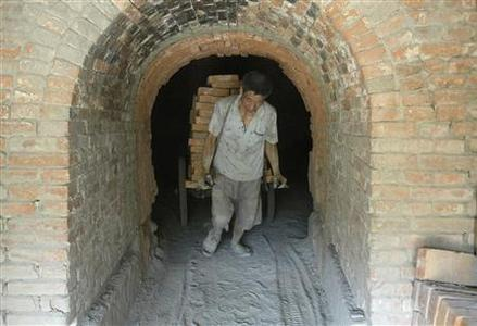 A paid labourer transports bricks at a brick kiln in Baokang, central China's Hubei province June 16, 2007. Chinese police have captured a man accused of holding workers in virtual slavery, state media reported on Sunday amid a national uproar over teenagers and men forced to work in brutal, furnace-like brick kilns. REUTERS/Stringer