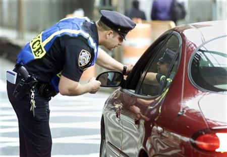 A police officer speaks with a driver in a file photo. A passenger in a car pulled over for a traffic violation can challenge the stop for violating the constitutional protection against unreasonable searches and seizures, the Supreme Court ruled unanimously on Monday. REUTERS/Shannon Stapleton