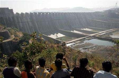 A file photo of people looking at the Sardar Sarovar Narmada dam in Kavadia, 194 km (121 miles) south of the Indian city of Ahmedabad, December 31, 2006. India's greenhouse gas emissions could be 40 percent higher than official estimates if methane released from dams is taken into account, according to a new study. REUTERS/Amit Dave