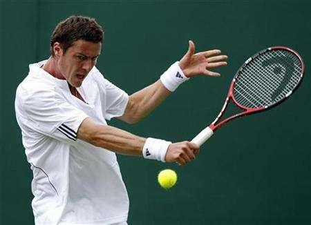 In this file picture, Russia's Marat Safin returns a shot to South Africa's Rik De Voest at the Wimbledon tennis championships in London June 26, 2007. Safin has won more than $13 million in prize money in his tennis career but said he could hardly afford a meal at this year's Wimbledon. REUTERS/Alessia Pierdomenico