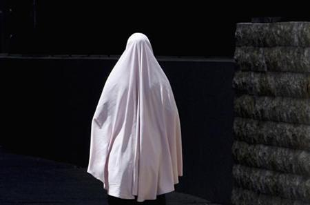 A woman wearing a hijab walks into Sydney's Lakemba Mosque for midday prayers, October 27, 2006. Australia has a bigger portion of Muslim youths at risk of turning to radical Islam than any other Western nation, with up to 3,000 in ''ideological sleeper cells'' in Sydney alone, a government-backed study said on Monday. REUTERS/David Gray