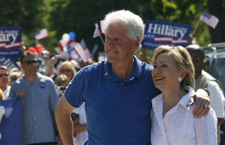 Democratic Presidential candidate and U.S. Senator Hillary Clinton (D-NY) and her husband, former U.S. President Bill Clinton, smile to supporters during the 4th of July parade in Clear Lake, Iowa, July 4, 2007. REUTERS/Joshua Lott