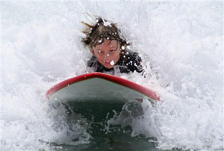 A young boy tries to catch a wave while cooling off under sunny sky's and hot temperatures at the beach in Leucadia, California July 3, 2007. REUTERS/Mike Blake