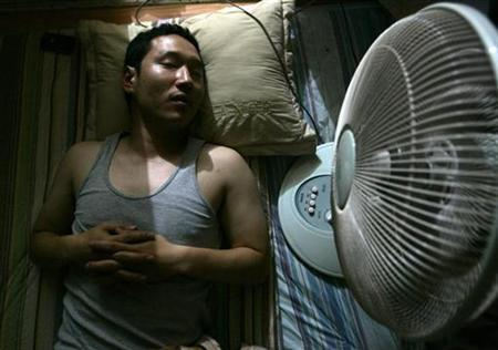 A man lies next to an electric fan in his home in Seoul July 4, 2007. Summertime in South Korea means cold beer on steamy nights and lonely deaths in stuffy rooms blamed on electic fans. Electric fans and Koreans are a deadly combination, according to an urban legend in the country that has it if a person sleeps in a closed room with a fan on all night they may never wake up. REUTERS/Han Jae-Ho