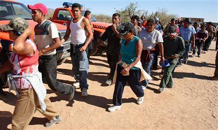 Mexicans walk across the desert near the town of Sasabe heading towards the U.S. border at Arizona in this May 24, 2006 file photo. Tougher security along the U.S.-Mexico border is forcing migrants to take more dangerous, remote routes to cross into the United States and pushing up the number of deaths in the desert. REUTERS/Daniel Aguilar