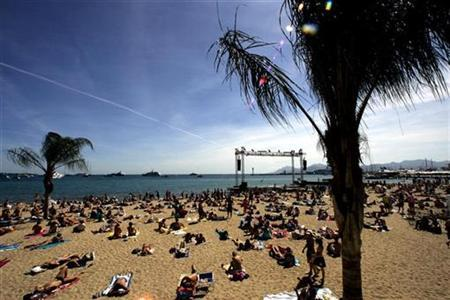 People lay on a beach in Cannes, France, May 17, 2007. Global warming could trigger hurricanes, or tropical cyclones, over the Mediterranean sea, threatening one of the world's most densely populated coastal regions, according to European scientists. REUTERS/Eric Gaillard