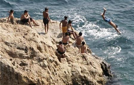 Kids jump into the water from a rock along the Mediterranean coast in the city of Antalya, July 6, 2007. REUTERS/Fatih Saribas