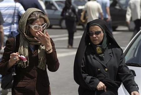 A policewoman (R) warns a woman about the state of her clothing and hair during a crackdown on adhering to the strict Islamic dress code in Tehran in this April 22, 2007 file photo. Iranian police stepped up a crackdown on Monday on women ignoring strict Islamic dress codes, including sending newly trained women officers to help ''guide'' violators, a police official said. REUTERS/Stringer