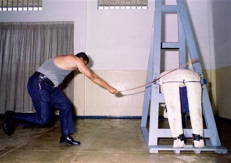 A prison services officer demonstrates the caning procedure on a dummy inside Singapore's Changi Prison in an undated file photo. A Singapore judge has been punished for mistakenly sentencing a prisoner to an extra three strokes of the cane, the Singapore government said Tuesday. REUTERS/New Paper/Handout