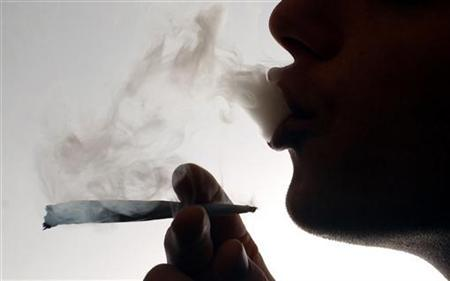 An unidentified man smokes a cannabis cigarette at a house in London before the relaxation of cannabis laws, in this file photo from January 24, 2004. Smoking one cannabis joint is as harmful to a person's lungs as having up to five cigarettes, according to research published on Tuesday. REUTERS/David Bebber