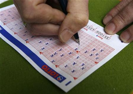 A man fills in a lottery ticket at a Lotto receiving office in Dortmund in this October 6, 2006 file photo. REUTERS/Ina Fassbender