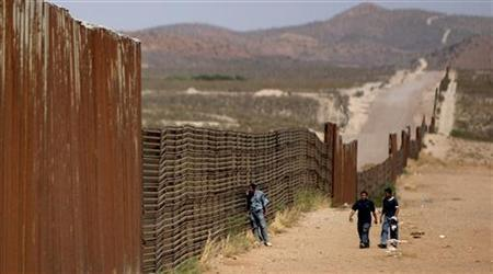 Mexican men walk along the border wall that separates Agua Prieta, Sonora, Mexico from Douglas, Arizona, U.S., May 23, 2006. A U.S. Border Patrol agent must stand trial for murder in the shooting of a Mexican man trying to enter the United States, an Arizona judge ruled Monday in a case that drew criticism from Mexico. REUTERS/Daniel Aguilar