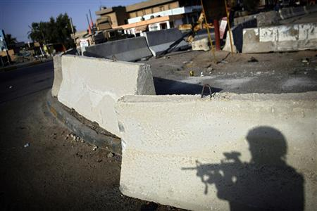 A U.S. soldier from the 2nd battalion, 32nd Field Artillery brigade casts a shadow on an empty intersection during a patrol in Baghdad August 6, 2007. REUTERS/Damir Sagolj
