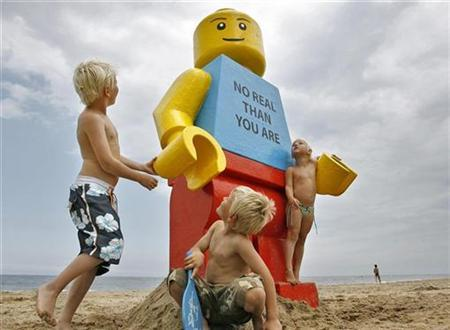 Children play near a giant smiling Lego man that was fished out of the sea in the Dutch resort of Zandvoort August 7, 2007. Workers at a drinks stall rescued the 2.5-metre (8-foot) tall model with a yellow head and blue torso. The toy was later placed in front of the drinks stall. REUTERS/Marco de Swart