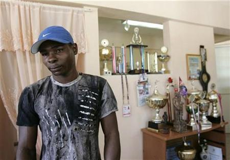 Guillermo Rigondeaux, two-time bantamweight Olympic champion, stands next to his trophies at his home in Havana, August 8, 2007. REUTERS/Enrique De La Osa