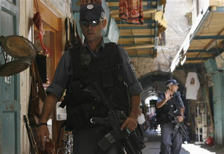 Israeli policemen examine the scene of a gun attack in Jerusalem's Old City August 10, 2007. A man grabbed a gun from an Israeli security guard and shot him in Jerusalem's Old City on Friday, sparking a gun battle in which the attacker was killed and at least 10 others injured, police and medics said. REUTERS/Eliana Aponte