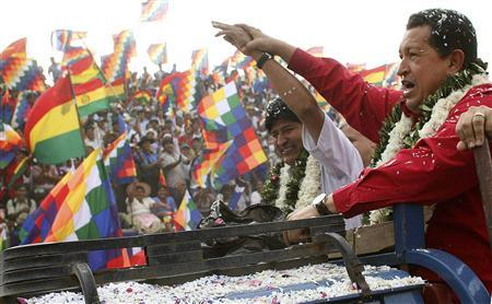 Venezuela's President Hugo Chavez (R) and his Bolivian counterpart Evo Morales ride on the back of a pickup truck as Bolivians cheer during their arrival in the village of Entre Rios in the Chapare region, some 372 miles southeast of La Paz, August 10, 2007. REUTERS/Miraflores Palace/Handout