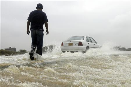 A man wades through flood water after heavy rains in Karachi, August 11, 2007. Scientists are trying to improve predictions about the impact of global warming this century by pooling estimates about the risk of floods or desertification. REUTERS/Athar Hussain