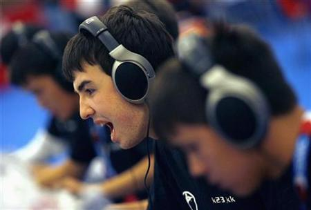 A youth reacts as he plays video games during a competition in Paris, July 5, 2007. Children in Europe are aware of the risks of illegal downloading, but often rationalize their act by saying that everyone -- including their parents -- is doing it, according to a major European Commission survey. REUTERS/Jean-Paul Pelissier