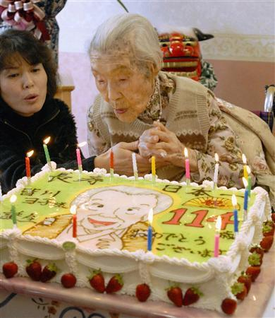 Yone Minagawa blows off some of the candles on her birthday cake with a nursing home official as they celebrate her 114th birthday in southwestern Japan, January 4, 2007. Minagawa, recognized by Britain's Guinness World Records as the world's oldest person at the age of 114, died on Monday evening, Kyodo news agency reported informed sources as saying. REUTERS/Kyodo