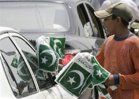 A boy sells Pakistani national flags at a road intersection on the eve of the country's Independence Day in Islamabad August 13, 2007. REUTERS/Faisal Mahmood