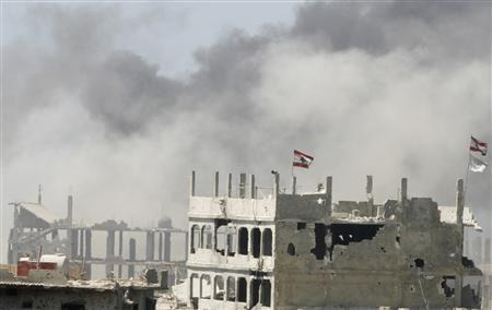 Lebanese flags are seen on top of buildings of the bombarded Nahr al-Bared refugee camp during clashes with al Qaeda-inspired militants of Fatah al-Islam in north Lebanon July 18, 2007. The United States said on Monday it had designated Fatah al-Islam as a ''terrorist'' organization, subjecting it to U.S. financial sanctions. Over the last 12 weeks, Fatah al-Islam has been fighting the Lebanese army at the Nahr al-Bared refugee camp in clashes that have killed at least 278 people and displaced some 40,000 refugees. REUTERS/Omar Ibrahim