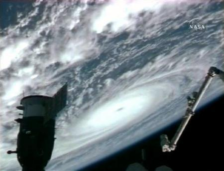 The International Space Station is silhouetted with the earth in the background where hurricane Flossie and its eye can be seen swirling towards Hawaii in this view from NASA TV August 12, 2007. The National Weather Service put the island of Hawaii under a hurricane watch on Monday morning as Hurricane Flossie continued on a course that should bring it within 100 miles of the Pacific state. REUTERS/NASA TV