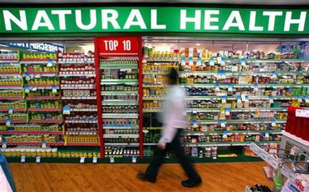 A store worker walks past rows of herbal, vitamin and mineral pill products at a suburban pharmacy in Sydney April 29, 2003. Middle-aged women at risk for heart disease received little benefit from taking vitamins C, E or beta carotene, researchers said on Monday. REUTERS/David Gray