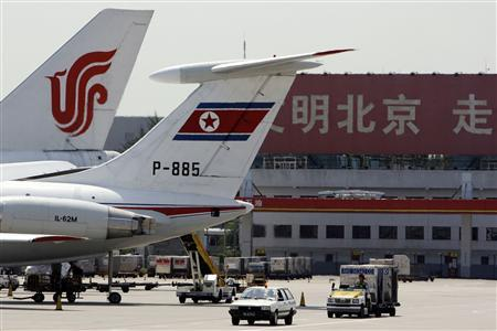 Airport workers drive their vehicles along the tarmac past a Chinese Airlines (L) and North Korean Airlines plane at Beijing's International Airport, August 14, 2007. REUTERS/David Gray