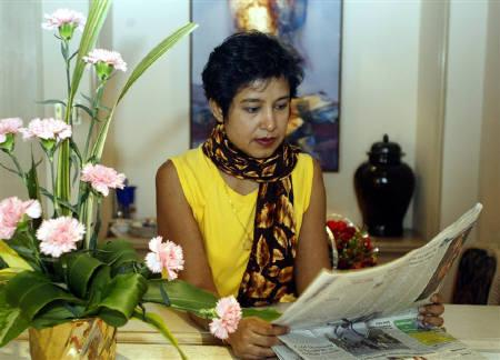 File photo of Bangladeshi author Taslima Nasreen reading a newspaper in a hotel in Kolkata, January 20, 2004. Muslim clerics in eastern India issued a ''death warrant'' against controversial Bangladeshi author Taslima Nasreen on Friday, threatening her life if she did not leave the country where she lives in exile. REUTERS/Jayanta Shaw/Files