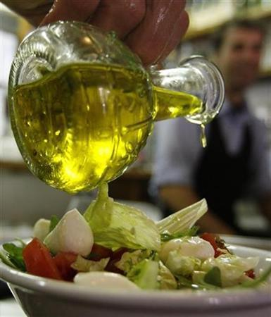 A diner pours olive oil on a salad at a restaurant in Rome May 17, 2007. Eating foods prepared with olive oils that are rich in phenols, substances though to have beneficial effects on the heart, may help ward off harmful blood clots in people with high cholesterol, Spanish researchers report. REUTERS/Dario Pignatelli