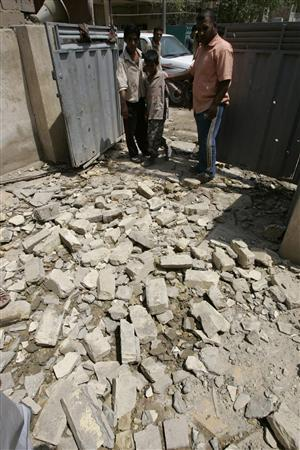 Residents stand near the rubble of a house that was damaged after a mortar attack in Baghdad August 19, 2007. REUTERS/Kareem Raheem