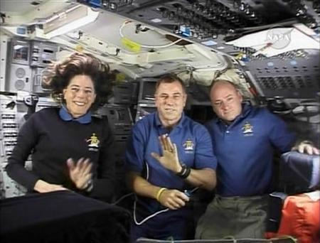 Space Shuttle Endeavour astronauts Barbara Morgan (L), Dave Williams (C) of the Canadian Space Agency and shuttle Commander Scott Kelly (R) wave to Canadian school children on the aft flight deck of the orbiter in this view from NASA TV August 20, 2007. REUTERS/NASA TV (