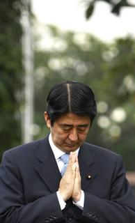 Japan's Prime Minister Shinzo Abe prays in front of the grave of a Japanese soldier at the Hero Cemetery in Jakarta August 21, 2007.   REUTERS/Beawiharta
