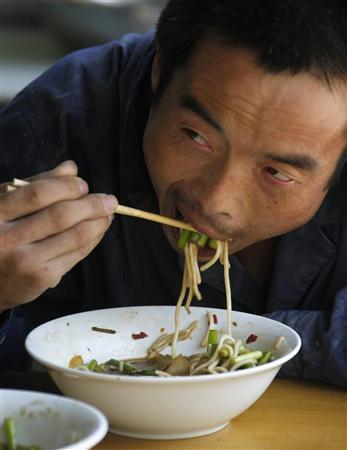 A construction worker eats noodles with disposable chopsticks at a roadside food stall in Beijing, August 22, 2007. A Beijing factory recycled used chopsticks and sold up to 100,000 pairs a day without any form of disinfection, a newspaper said on Wednesday, the latest in a string of food and product safety scares. REUTERS/Jason Lee