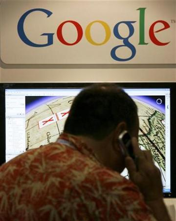 A convention attendee talks on a cell phone as he views a display of Google Maps at SIGGRAPH 2007 in San Diego, California August 9, 2007. Google Inc has seen a spike in usage of its mobile services since May, partly offsetting the traditional summer slump in computer-based Web surfing for the first time, an executive said on Wednesday. REUTERS/Mike Blake