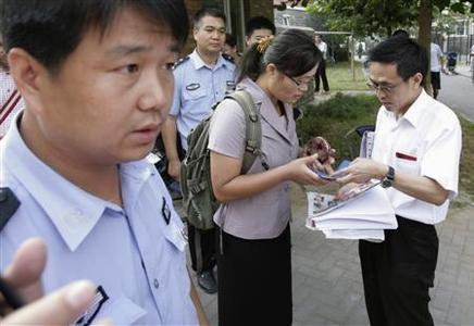 Yuan Weijung (C), the wife of blind Chinese activist Chen Guangcheng, who is serving a four-year prison term after exposing forced abortions and sterilisation in northern China in 2005, is checked by uniformed and plainclothes policemen as she leaves her home followed by in Beijing, August 24, 2007. China on Friday prevented her from going to the Philippines to collect a human rights award on behalf of her husband after they revoked her passport. REUTERS/Reinhard Krause