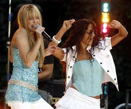 Miley Cyrus (L), star of The Disney Channel's series ''Hannah Montana'', performs in New York, June 22, 2007. The Los Angeles comedy writer-producer who penned Fox's ''In Living Color'' and created Nickelodeon's ''Roundhouse'' has sued the Walt, claiming it stole the idea for its hit Disney Channel show, ''Hannah Montana,'' from him. REUTERS/Shannon Stapleton
