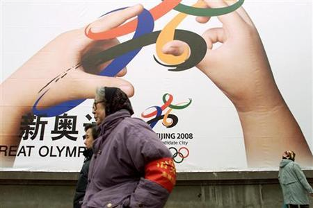 An elderly woman (wearing red armband), who serves as a guardian against illegal practices in her neighborhood, patrols in front of a giant poster promoting Beijing's bid for the 2008 Olympic Games, February 22, 2001. China's capital will replace Communist-era red armbands worn by hundreds of thousands of security volunteers with stylish Olympic badges ahead of the 2008 Summer Games, local media said on Friday. REUTERS/Andrew Wong