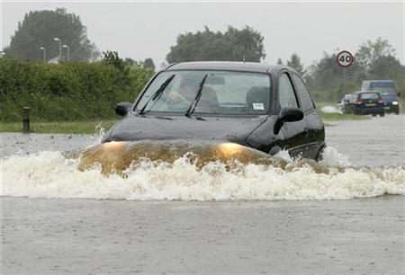 A car is driven through flood water on the A1079 in Market Weighton near Hull, June 25, 2007. Cities need to review their drainage systems in the wake of this summer's floods to cope with the possibility of more extreme weather due to climate change, a report said on Friday. REUTERS/Nigel Roddis