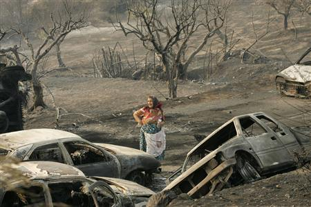 An elderly woman stands amongst burnt cars in the village of Artemida in Peloponnese peninsula, southwest of Athens August 25, 2007. The worst forest fires to hit Greece in decades have killed 41 people and more are feared dead, authorities said on Saturday. REUTERS/John Kolesidis